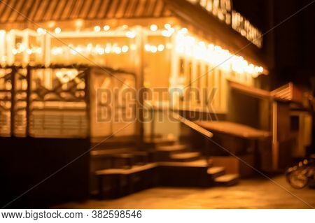 Street Cafe At Night In The Light Of Blurry Holiday Lights. Festive Defocused Blurred Background