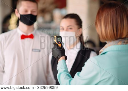 The Manager Of A Restaurant Or Hotel Checks The Body Temperature Of The Staff With A Thermal Imaging