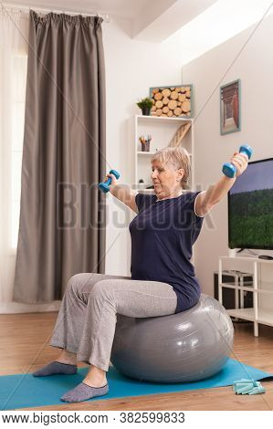 Senior Woman Using Balance Ball And Dumbbells Sitting On Yoga Mat At Home. Old Person Pensioner Onli