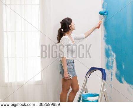 Caucasian Woman Redecorating Apartment And Painting Walls With Roller Brush. Apartment Makeover. Red