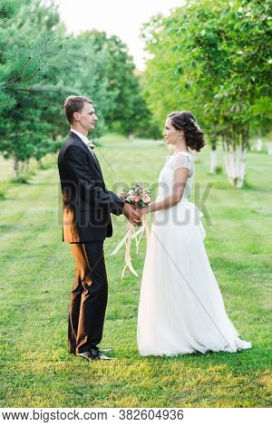 Just Married Loving Couple In Wedding Dress And Suit On Green Field In A Forest At Sunset. Happy Bri