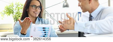 Businessman And Businesswoman Are Sitting At Table In Office Having Dialogue. Planning A Business St