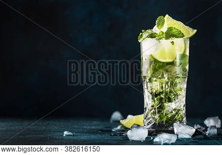 Mojito Cocktail Or Mocktail With Lime, Mint, And Ice In Glass On Blue Background. Summer Cold Alcoho