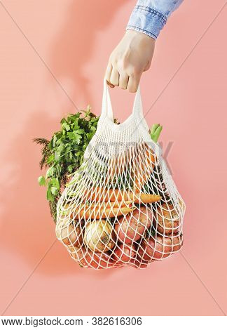 Mesh Bag With Vegetables And Herbs In Female Hand. Woman Hold String Net Shopping Bag On Pink Backgr