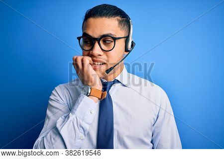 Young brazilian call center agent man wearing glasses and tie working using headset looking stressed and nervous with hands on mouth biting nails. Anxiety problem.
