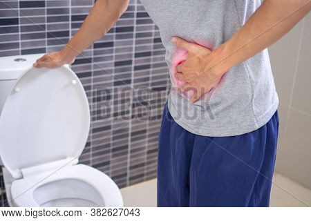 Men Are Standing With Their Bellies In Front Of The Toilet In The Bathroom. There Is Severe Abdomina
