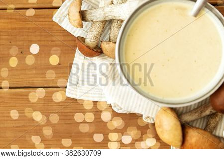 food cooking, eating and culinary concept - mushroom cream soup in bowl on wooden cutting board