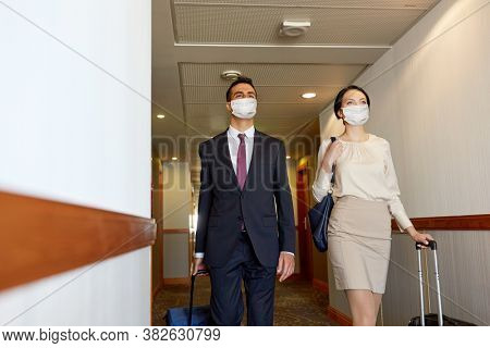 business trip, health and people concept - man and woman with travel bags at hotel corridor wearing face protective medical mask for protection from virus disease