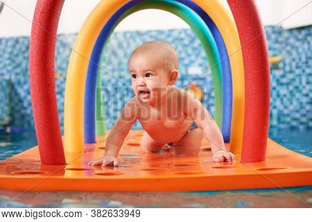 Happy Child Crawling On Floating Colorful Construction In The Swimming Pool. Cute Kid Smiling While