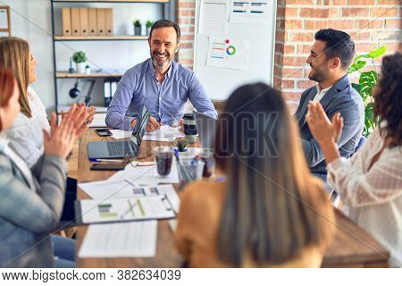 Group of business workers smiling happy and confident. Working together with smile on face applauding one of them at the office