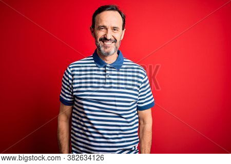 Middle age hoary man wearing casual striped polo standing over isolated red background with a happy and cool smile on face. Lucky person.