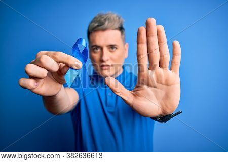 Close up of young man holding colon cancer awareness blue ribbon over isolated background with open hand doing stop sign with serious and confident expression, defense gesture
