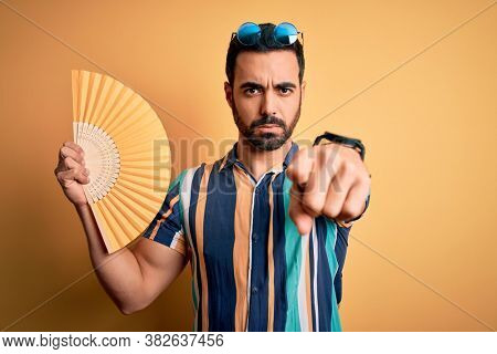 Young handsome tourist man with beard on vacation wearing summer shirt using hand fan pointing with finger to the camera and to you, hand sign, positive and confident gesture from the front