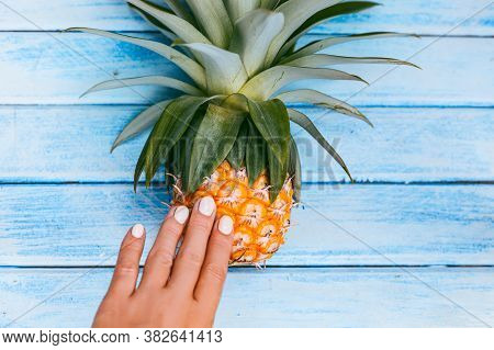 Fresh Pineapple Lying On Blue Wooden Background And Woman Hand Touching It