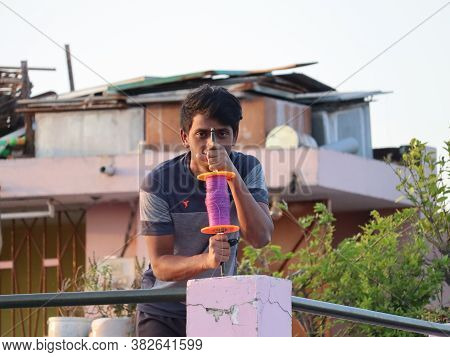Mumbai, Maharastra/india- April 16 2020: A Boy Holding The Kite Thread While Standing On The Rooftop