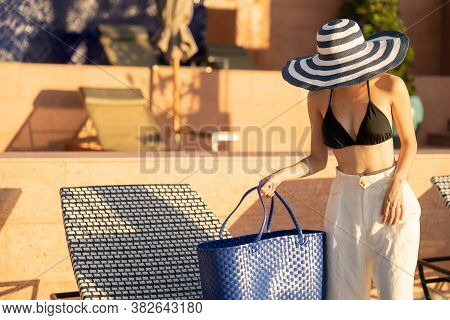 Women Standing Near Sunbathing Bed With Straw Bag For Sunbathing On Beach.
