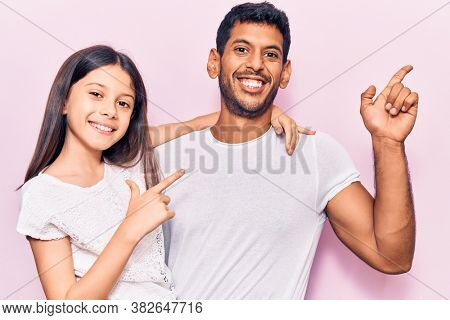 Latin father and daughter wearing casual clothes cheerful with a smile of face pointing with hand and finger up to the side with happy and natural expression on face
