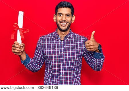 Young latin man holding graduate degree diploma smiling happy and positive, thumb up doing excellent and approval sign