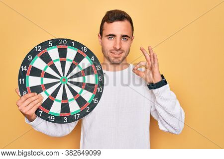 Young handsome man with blue eyes holding dartboard over isolated yellow background doing ok sign with fingers, excellent symbol