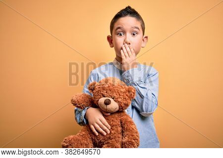 Young little boy kid hugging teddy bear stuffed animal over yellow background cover mouth with hand shocked with shame for mistake, expression of fear, scared in silence, secret concept