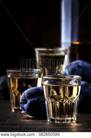 Slivovica - Plum Brandy Or Plum Vodka, Hard Liquor, Strong Drink In Glasses On Old Wooden Table, Fre