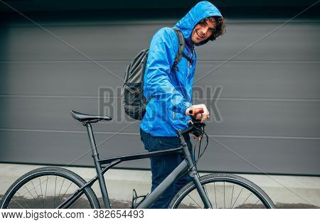 Side View Image Of A Smiling Handsome Young Man Walking With His Bike Before Bicycling On A Rainy Da
