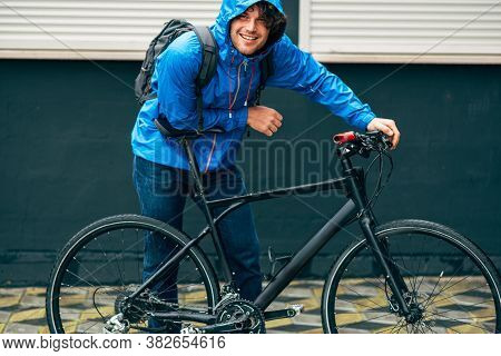 Outdoor Shot Of Smiling Handsome Man In Blue Raincoat Posing With His Bike After Bicycling Down The