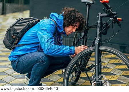 Young Curly Man Fixing With His Bike After Bicycling Down The Street On A Rainy Day In The City Stre
