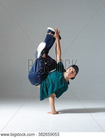 Cool B-boy Dancing On One Hand In Studio Isolated On Gray Background. Breakdance Poster