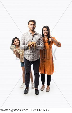 Indian Young Couple With Daughter Holding Gold Jewelry Or Ornaments In Hand