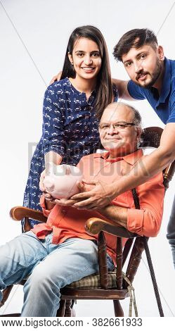Indian Asian Senior Man With Piggy Bank And Kids While Sitting On Rocking Chair