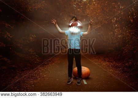 Jack-o-lantern - symbol of Halloween. A boy with a pumpkin a lantern on his head is walking along a road in the forest at dusk. Halloween.