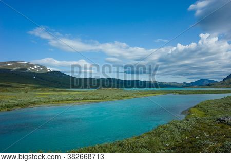 Swedish Lapland landscape. Turquoise water of Lake Alisjavri on Kungsleden and Nordkalottruta Arctic hiking Trail in northern Sweden. Arctic environment of Scandinavia in warm summer sunny day