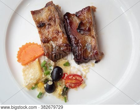 Pork Ribs Grilled With Bbq Sauce And Caramelized In Honey Served With A Side Dish On A White Plate.