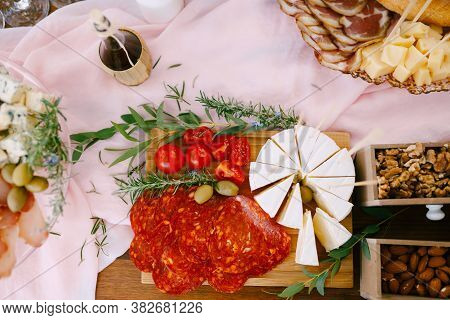 Top View Of A Cutting Board With Chorizo Sausage, Brie And Tomatoes Near Wooden Boxes Of Nuts And A
