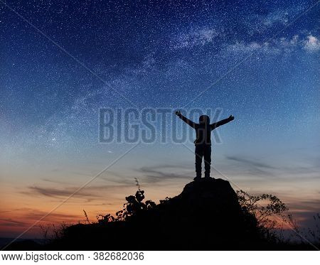 Silhouette Space Traveler Standing On Rocky Hill With Beautiful Night Sky On Background. Cosmonaut I