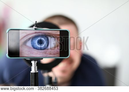 Close-up Of Man Looking In Magnifying Glass And Enlarges Eye. Detailed Picture Of Body Part On Smart