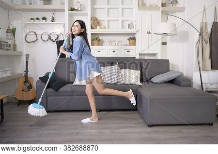 Happy Young Woman Cleaning Floor With Mop In Living Room
