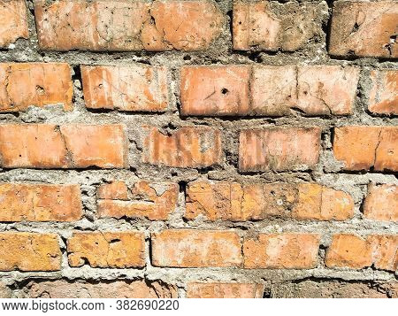 Part Of An Old Red Brick Wall With Cement. Close-up Old Brick Wall Texture. Wall Of Red Stones. Maso