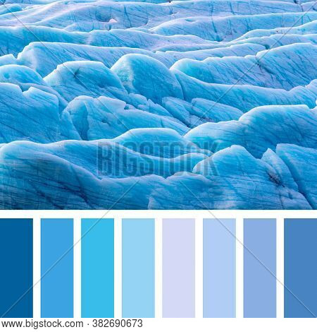 Sunlight catches the edges of blue glacial ice at the Svinafellsjokul glacier in southeast Iceland. In a colour palette with complimentary colour swatches.