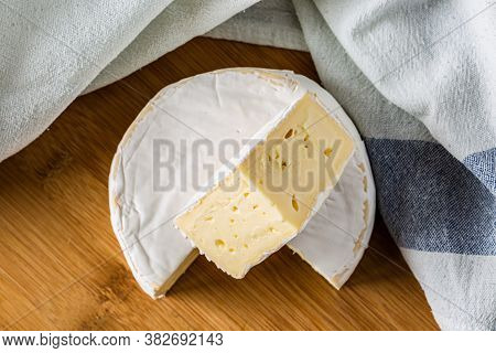 Fresh Brie Cheese And A Slice Close Up On Wooden Board