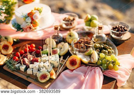 Cutting Board With Dorblue Cheese, Prosciutto And Cherry Tomatoes, On A Wooden Table With Fruit And