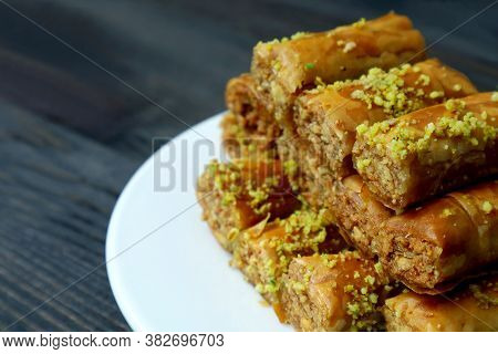 Closeup Pile Of Mouthwatering Baklava Pastries With Pistachio Nuts On A White Plate