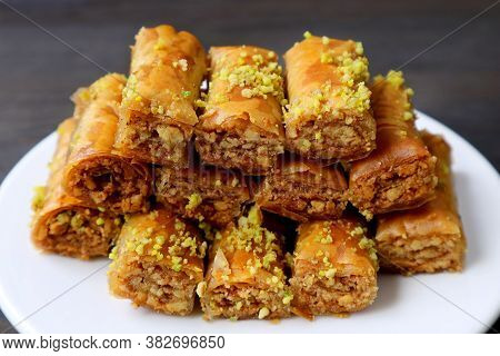 Plate Of Delectable Baklava Pastries Topped With Chopped Pistachio Nuts On Black Table