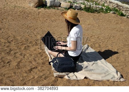 Young Woman Using Laptop Computer On Sunbed On A Beach. Freelance Work Concept, Freelancer Outside