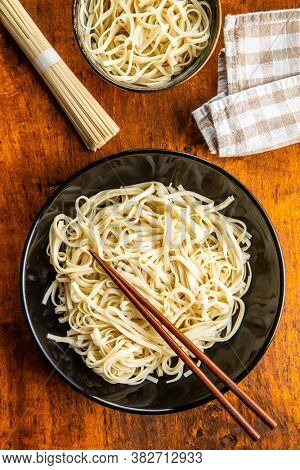 Cooked udon noodles. Traditional Japanese noodles in plate on wooden table. Top view.