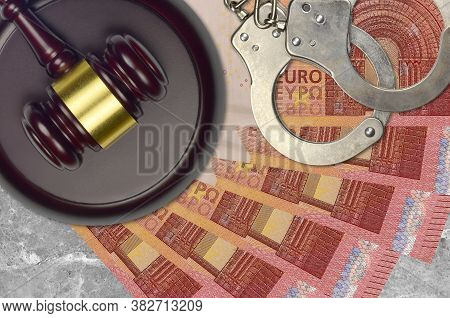 10 Euro Bills And Judge Hammer With Police Handcuffs On Court Desk. Concept Of Judicial Trial Or Bri