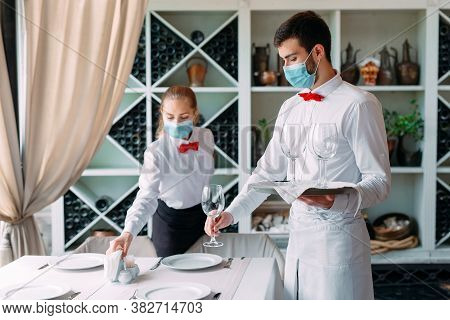 A Waiter In A Medical Protective Mask Serves A Table In The Restaurant. Employees Of A Restaurant Or