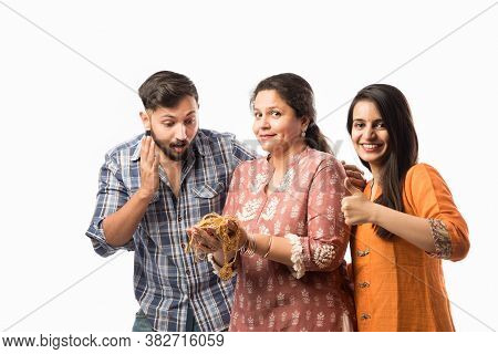 Gold Loan Or Mortgage Concept - Indian Mother With Son And Daughter Holding Gold Jewellery