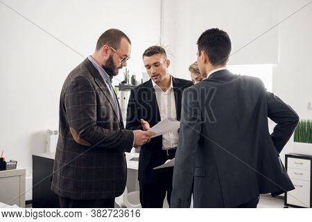 The Director Of The Company In A Jacket Gives Instructions And Tasks To Young Colleagues In The Offi